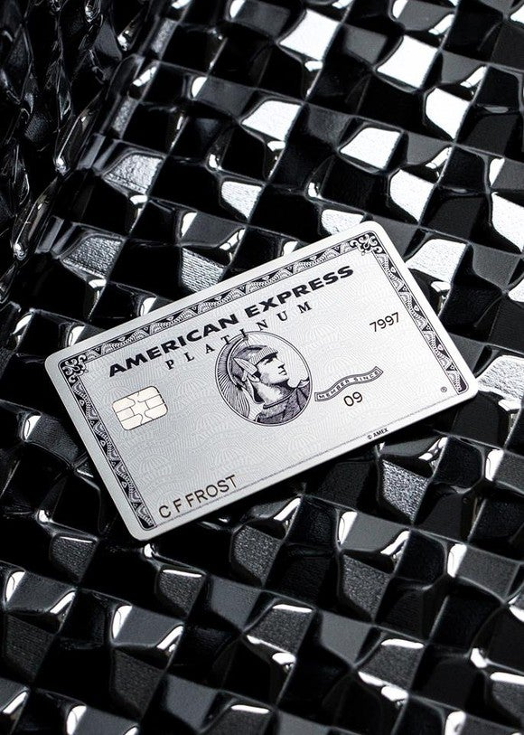 the American Express Platinum card, lying on a shiny black background