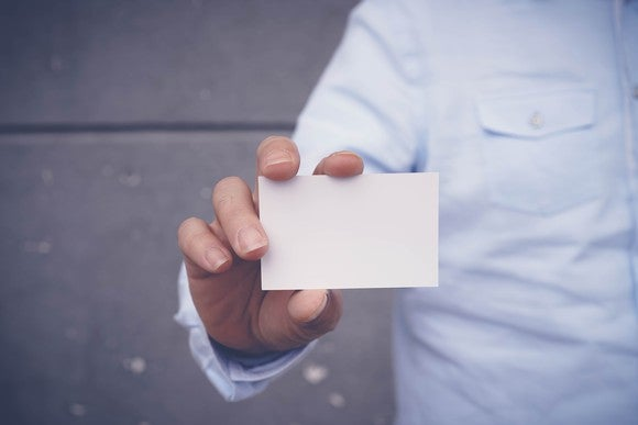man's hand holding out small blank white card
