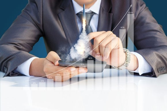 Businessman sitting behind a transparent growth chart, launching a rocket from his hand.