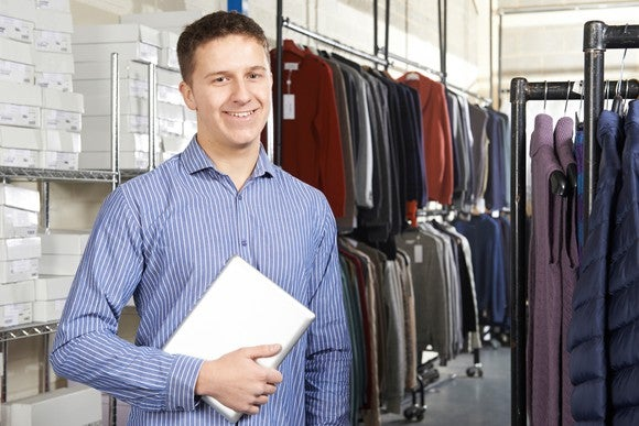 A warehouse worker stands among clothes.