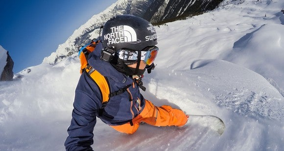 A snowboarder with a mounted GoPro as he goes down a ski slope.