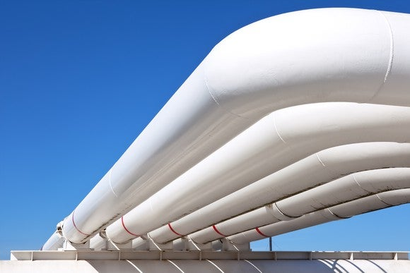 White gas pipelines with blue sky behind it.