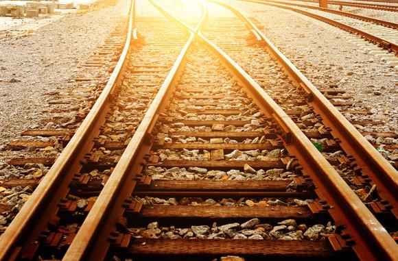 Rail road tracks with the sun shining down.