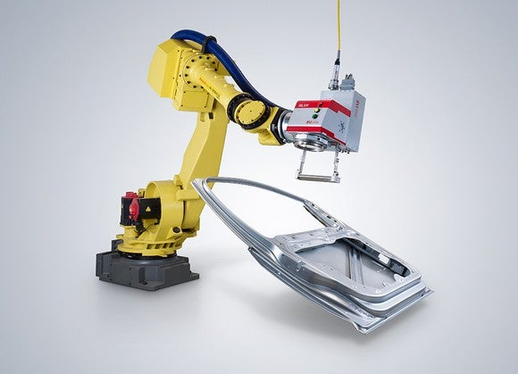 Yellow robotic arm wielding a laser in manufacturing an automobile doorframe.