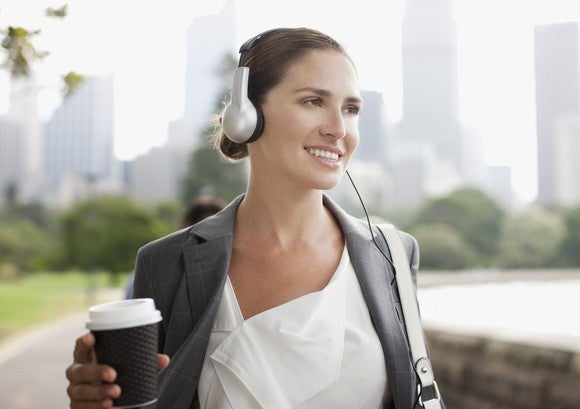 A woman wearing headphones and holding a cup of coffee while outside.