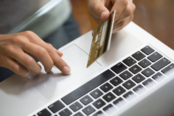 A hand holds a credit card over a laptop.