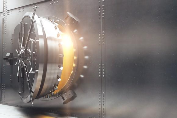 Bank vault door opening with light coming from inside.