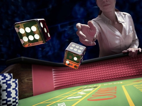 Woman rolling dice into a gaming table.