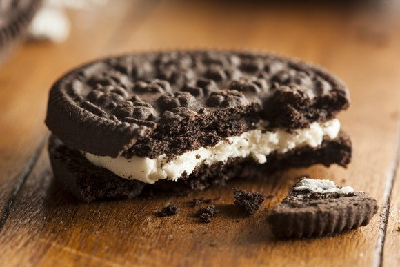 Broken chocolate cookie with cream filling on a table.
