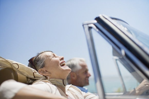 older couple smiling as they drive in a convertible