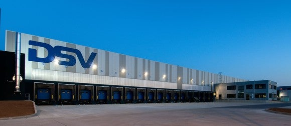 DSV distribution center showing empty truck bays with lights on near dawn.