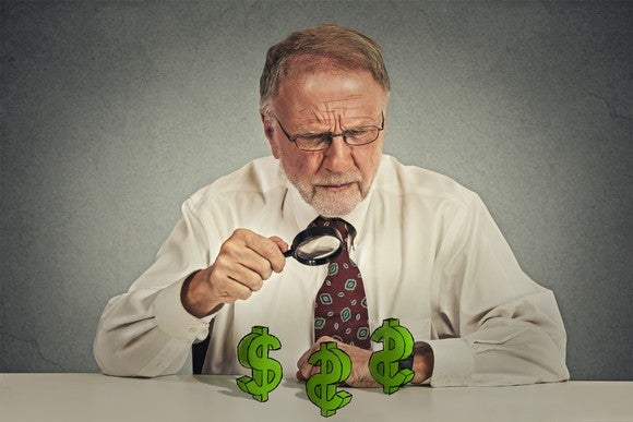 A senior man using a magnifying glass to examine dollar signs on a table.