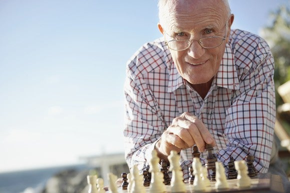A older man playing chess on the beach.