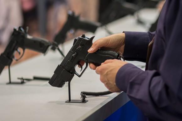 Hands holding a handgun on display