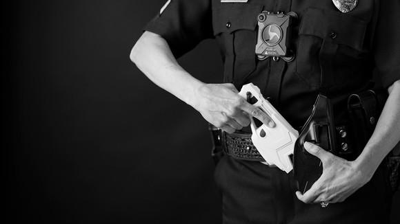 A police officer puts an Axon Enterprise TASER stun gun in a holster.