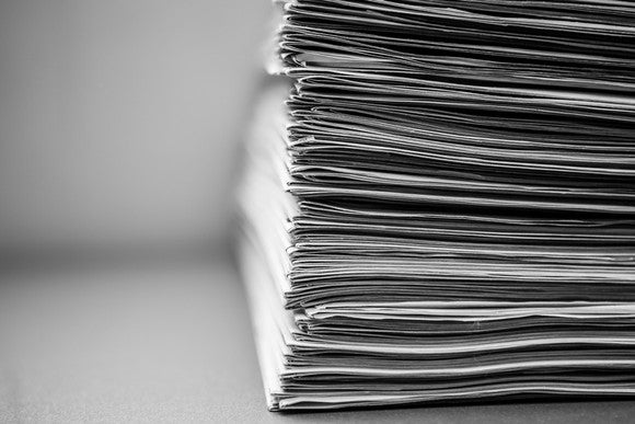 Newspapers stacked neatly in a tall pile, isolated on blurred white background.