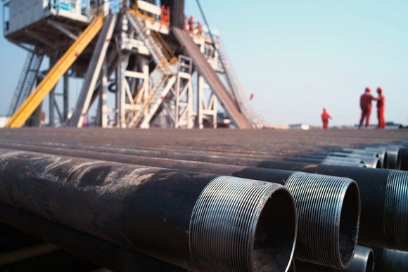 Stack of drilling pipe in front of a rig.