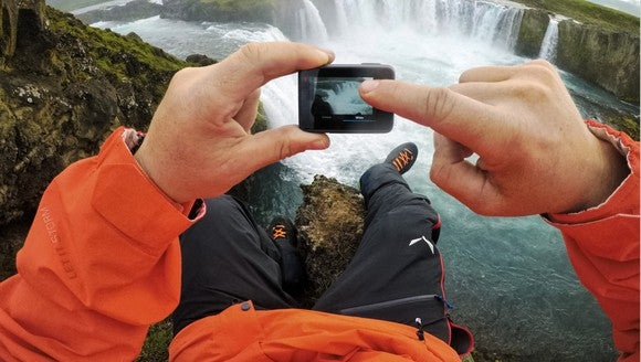 First-person view of man in orange coat using GoPro's HERO6 to take a video of a waterfall
