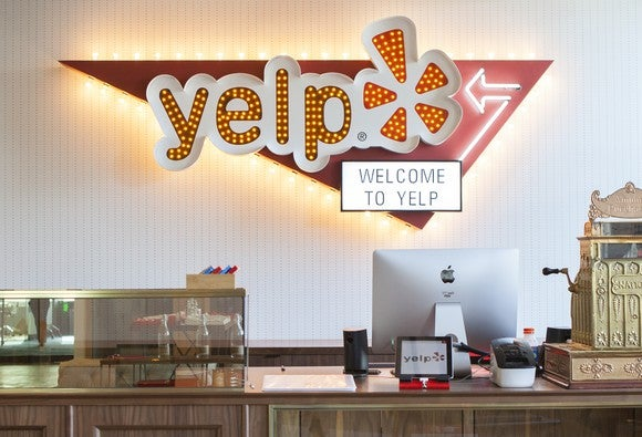 Yelp front desk with lit up logo on wall behind it
