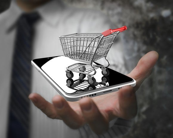 A person holding out a mobile phone with a miniature shopping cart on top of it