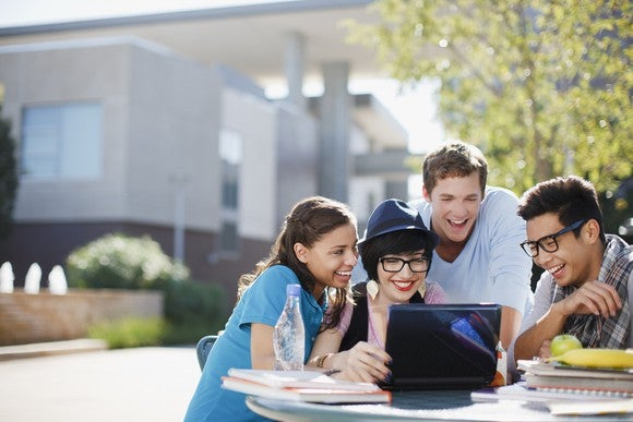 College-age people gathered around a laptop computer on a table outdoors.