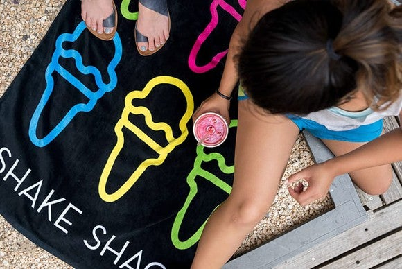 People sit on a Shake Shack beach towel.