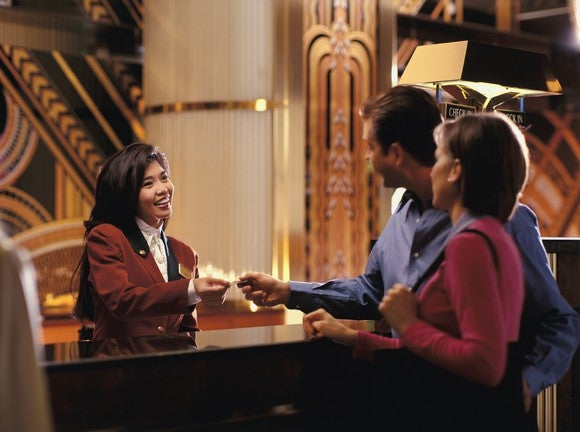 A couple is handed a room key at a hotel check-in desk.