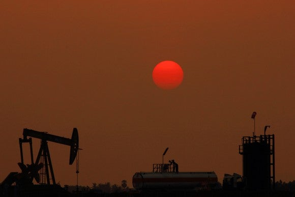 An oil pumping unit with a red moon in the background.