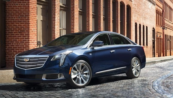 A dark blue Cadillac XTS sedan parked on a cobblestone city street.