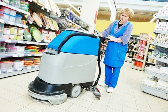 An employee cleans the floor at a retail store using a walk-behind scrubber.
