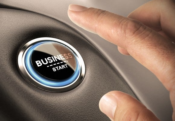 A person pushing a button with the words business and start on it