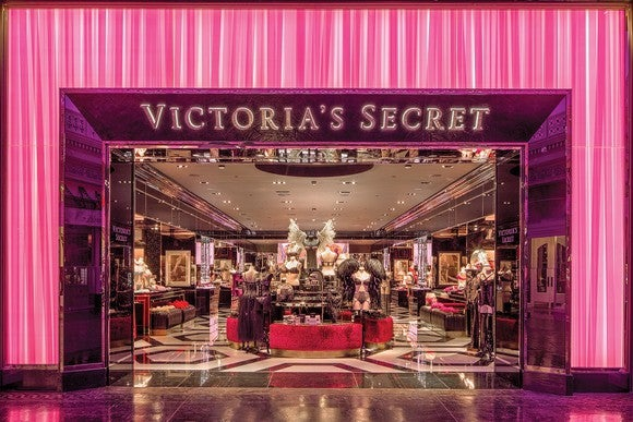 Outside of Victoria's Secret store, with pink trim and view of mannequins and clothing racks inside.