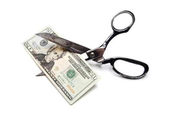 a pair of scissors cutting a 20 dollar bill
