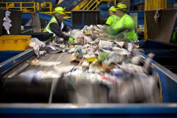 Workers separating paper and plastic on a conveyor belt in a recycling facility.
