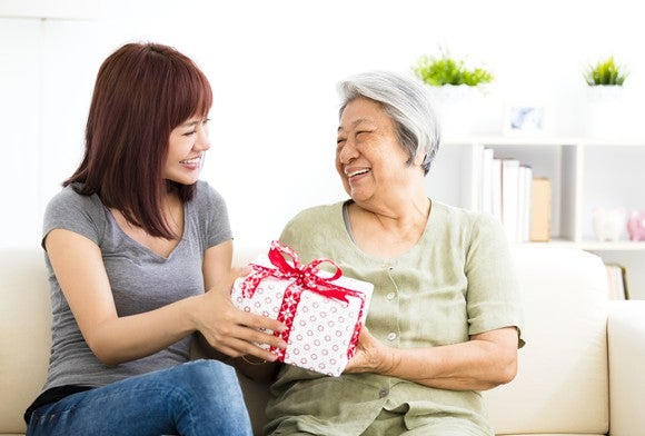 A woman gives a present to her mother.