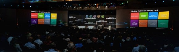 OpenText conference presentation, with speaker in front of large audience and colored displays showing a corporate presentation.