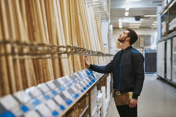 Carpenter looking at boards in home improvement store