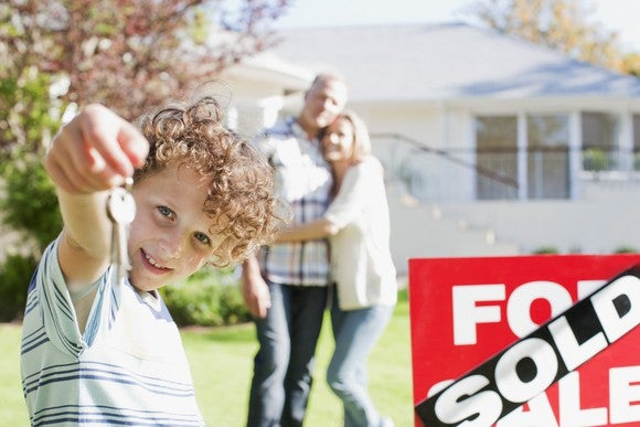 Family standing in front of house with sold sign. Child holding house keys and facing the camera.