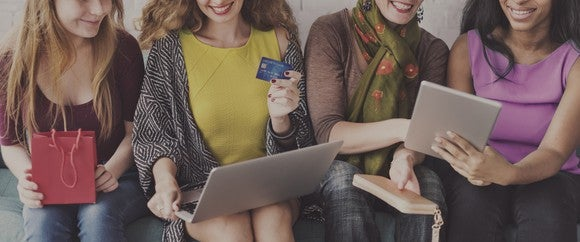 A line of women holding laptops and credit cards