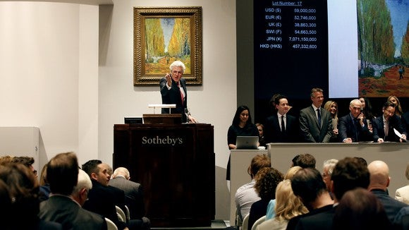 Auctioneer at podium pointing to the audience while selling a painting, with participants and other employees nearby.
