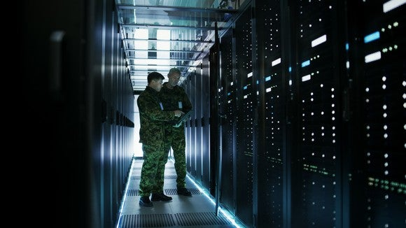 Two military officers stand between rows of mainframe computers in a data center.