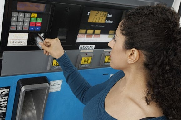 A woman paying with a credit card at gas station pump.
