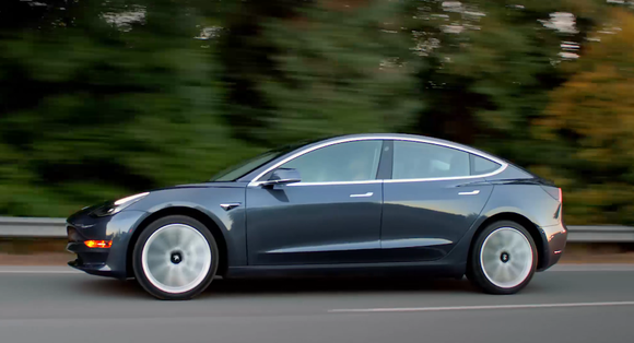 Side view of a black Model 3 driving on road with fall greenery in background.