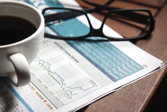 Financial papers with a cup of coffee and glasses.