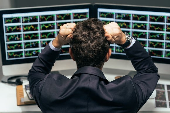 A man at a desk, seen from behind, presses his clenched hands against his head in apparent frustration as he looks at a number of stock charts on two computer monitors.
