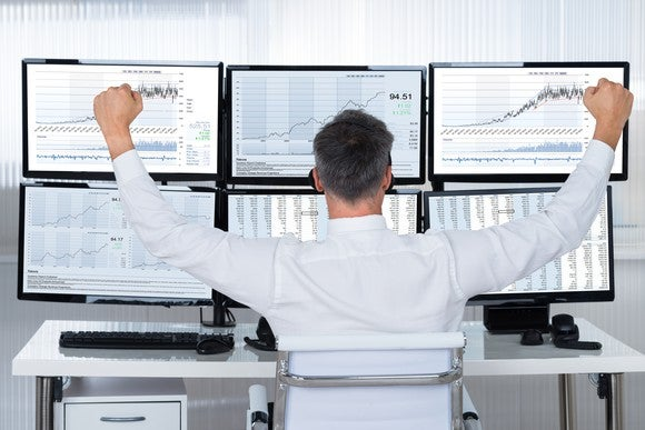 A man, seen from the back and seated at a desk, raises his clenched hands in a victory gesture as he looks at a bank of computer monitors.