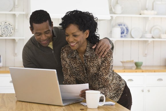 A man and woman smile while looking at a laptop sitting on a table. Also on the table is a coffee cup.