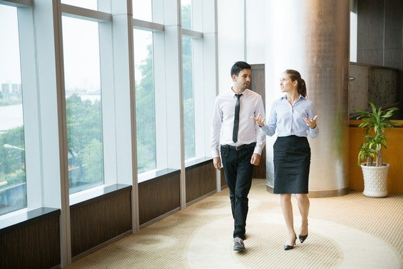 Businessman and businesswoman walking by large office windows discussing a matter.