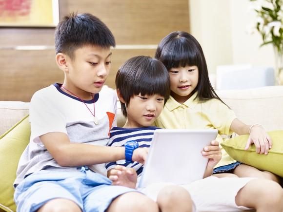 Three children gathered around a tablet computer
