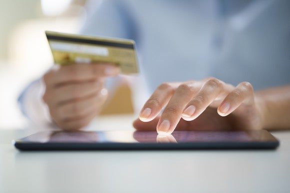 A man holds a credit card while typing into a tablet.